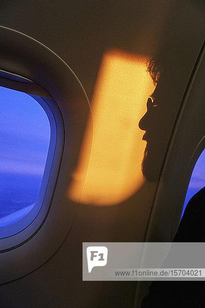 Schatten eines Mannes vor dem Fenster eines Flugzeugs