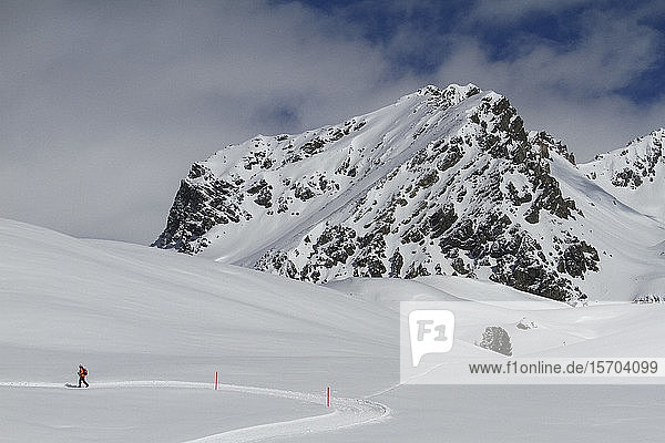 Snowshoer on sunny snowy mountain  Minschuns  Canton of Grisons  Switzerland