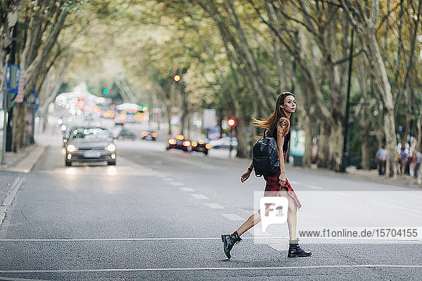 Young woman crossing city street