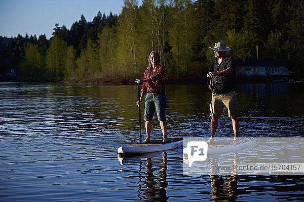 Couple standup paddleboarding on sunny lake  Shawnigan Lake  British Columbia  Canada