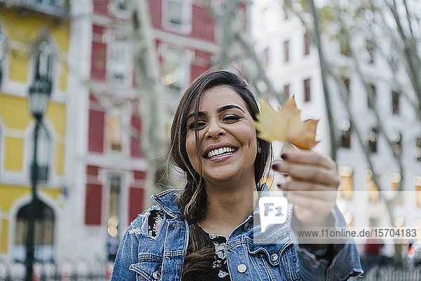 Portrait happy  playful young woman holding autumn leaf on urban street