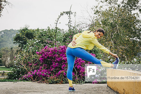Portrait fit female personal trainer exercising  stretching leg in park