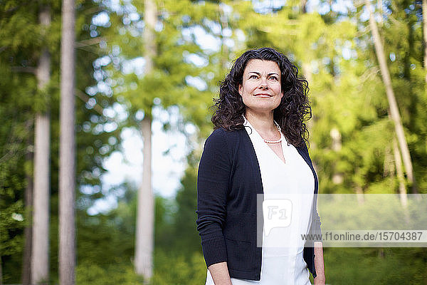 Portrait confident  serene woman in woods