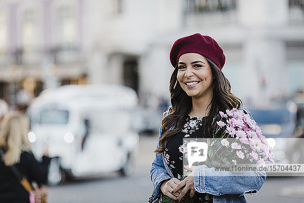 Portrait happy young woman in beret with flower bouquet on urban street