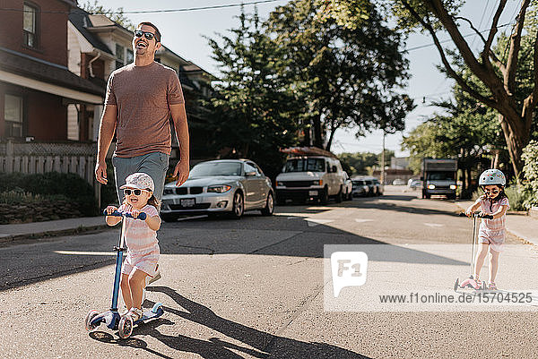 Father and daughters playing push scooter in neighbourhood