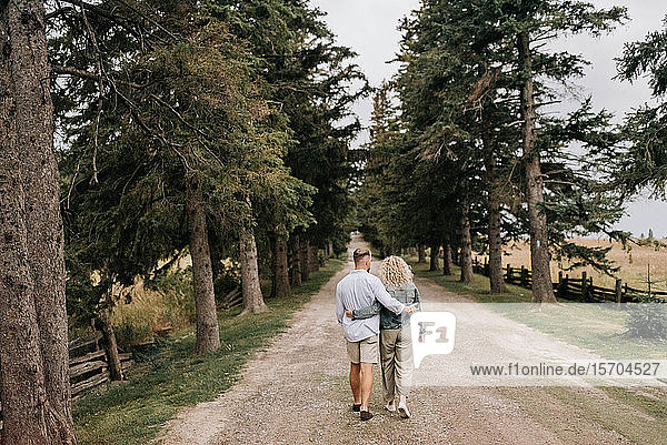 Young couple walking with hand around waist in countryside