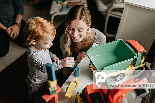 Mother and son playing with toy blocks in living room