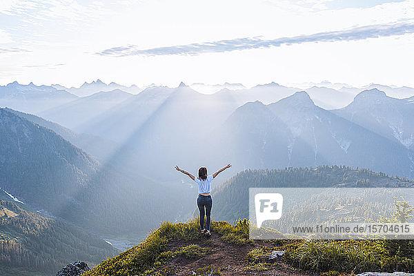 Wanderin  die auf dem Gipfel die Arme gegen die Sonne hebt  Winchester Mountain  North Cascades  Washington  USA