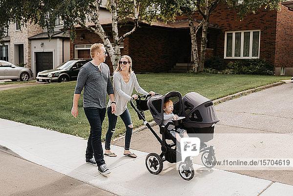 Paar nimmt Kleinkind im Kinderwagen mit zum Spaziergang in der Nachbarschaft