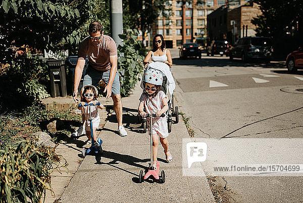 Paar und Töchter spielen in der Nachbarschaft Roller