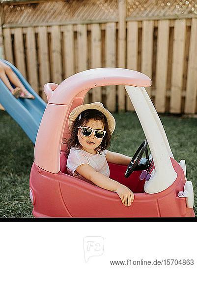 Toddler riding toy car in backyard