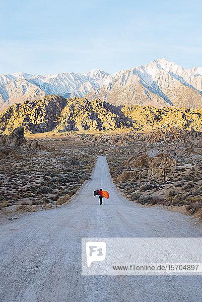 Frau mit farbenfroher Decke läuft bei Sonnenaufgang in der Wüste die Straße hinunter  Kalifornien  USA
