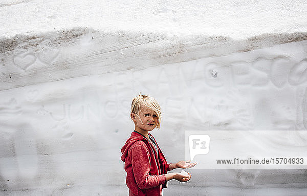 Child playing with snow in front of wall with scribblings