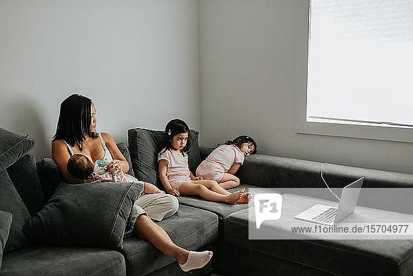 Mutter und Töchter entspannen sich auf der Couch im Wohnzimmer