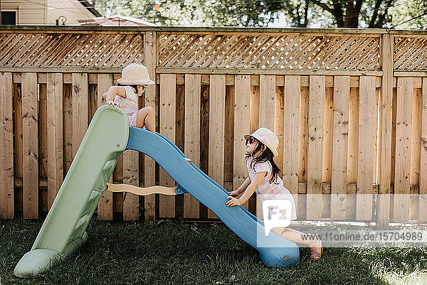 Sisters playing on slide in backyard