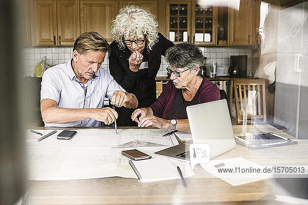 Weibliche Ausbilderin erklärt älteren Mann und Frau über Laptop am Tisch während des Navigationskurses