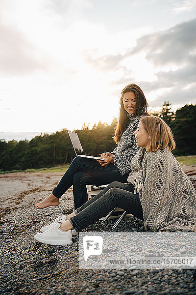 Smiling woman holding laptop while sitting with friend at beach during cold weather