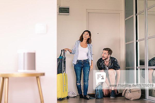 Aufgeregtes Paar mit Gepäck  das die Schuhe auszieht  während es sich in der Wohnung gegen die Türöffnung umsieht