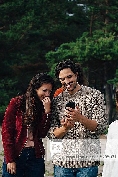 Lächelnder Mann zeigt einem Freund sein Smartphone  während er Urlaub macht