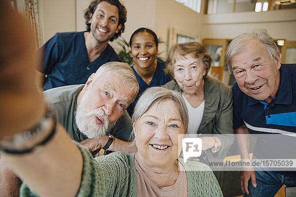 Ältere Frau im Ruhestand  die mit Freunden und Betreuern im Altenheim Selbsthilfe betreibt