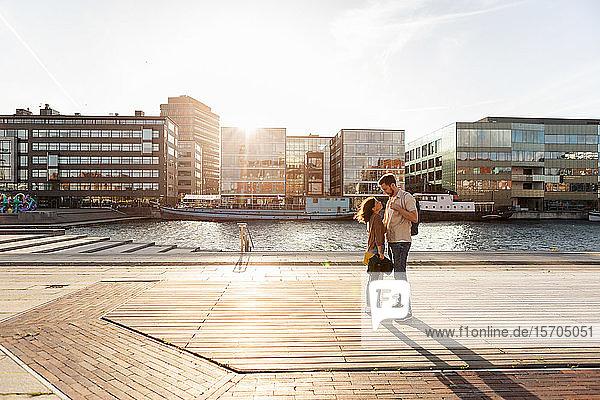 Liebespaar in voller Länge auf der Promenade am Fluss in der Stadt im Sommer