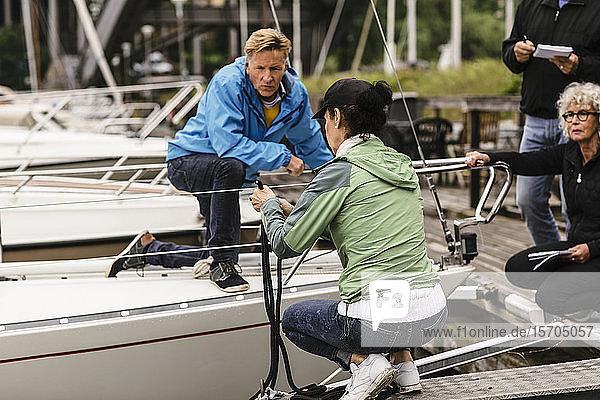 Älterer Mann und Frau betrachten weiblichen Ausbilder beim Binden eines Seils an der Reling einer Yacht während eines Bootsführerkurses