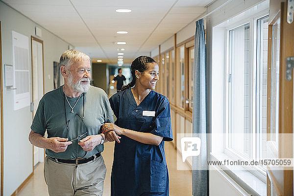 Lächelnder älterer Mann geht Arm in Arm mit einer Krankenschwester  während er in einer Gasse eines Pflegeheims wegschaut