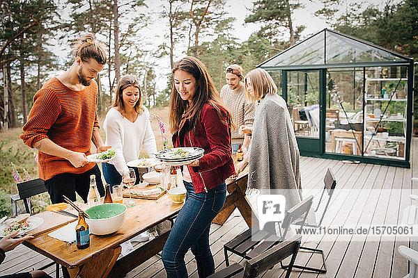 Männliche und weibliche Freunde  die nach dem Abendessen auf der Terrasse Tellerreste tragen
