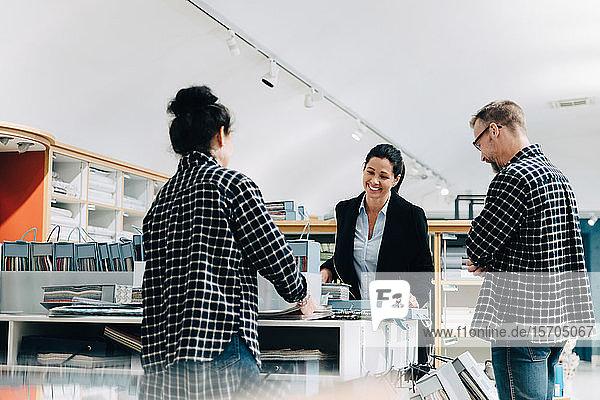 Verkaufsmitarbeiter unterstützen weibliche Kunden im Geschäft