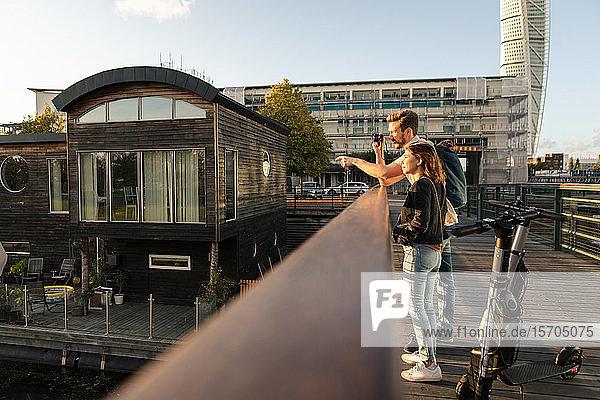 Oberflächenniveau eines fotografierenden Paares  das auf einer Brücke mit elektrischen Rollern in der Stadt steht