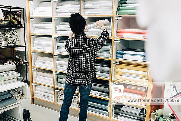 Rückansicht einer älteren Verkäuferin  die Tapeten im Regal anordnet