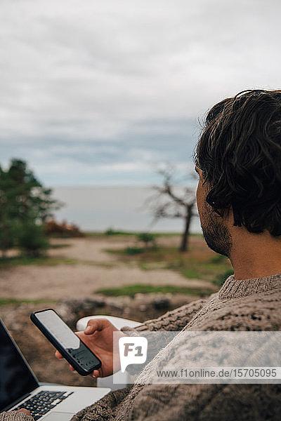 Nahaufnahme eines Mannes mit Laptop und Textnachrichten am Telefon  während er ins Freie schaut