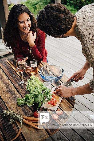 Mann im Gespräch mit lächelnder Frau beim Gemüseschneiden am Tisch im Innenhof