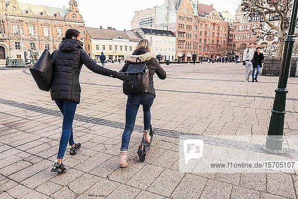 Freundin schiebt Teenager-Mädchen mit E-Scooter auf der Straße