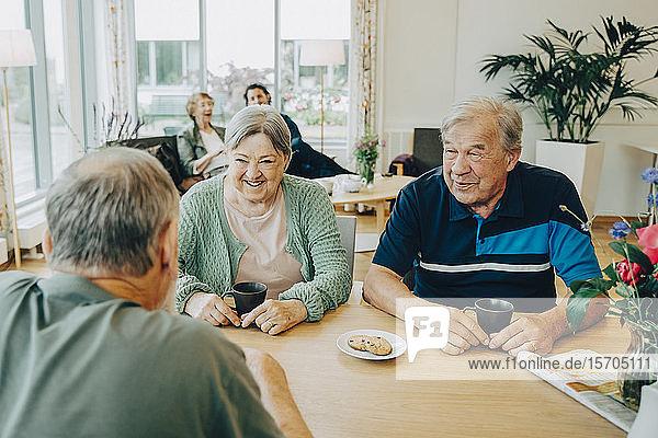 Ältere ältere Freunde unterhalten sich am Esstisch im Pflegeheim
