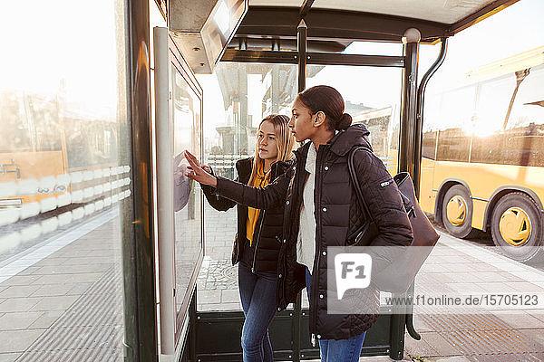 Freunde lesen Karte  während sie an einer Bushaltestelle in der Stadt stehen