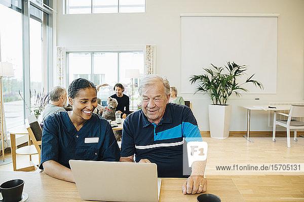 Lächelnde junge Gesundheitshelferin unterstützt älteren Mann bei der Benutzung des Laptops am Esstisch