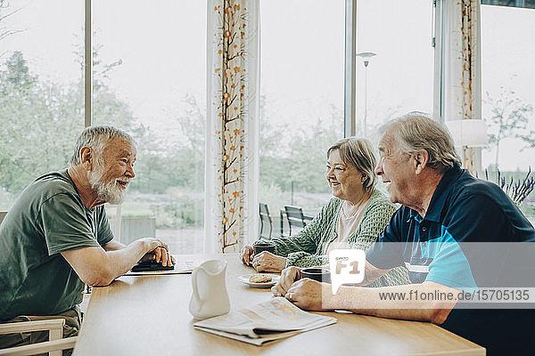 Seniorenfreunde im Ruhestand beim Gespräch am Esstisch im Pflegeheim
