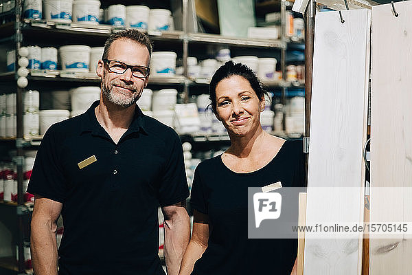 Portrait of smiling male and female employees standing in storage room