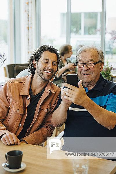 Älterer Mann  der sich mit seinem Enkel am Esstisch in einem Altenpflegeheim vergnügt