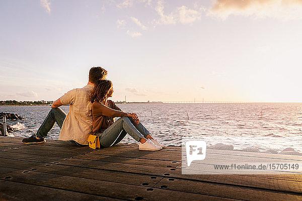 Ein Paar sitzt Rücken an Rücken auf einem Sitz und schaut bei Sonnenuntergang aufs Meer