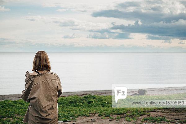 Rückansicht einer Frau  die das Meer gegen den Himmel betrachtet