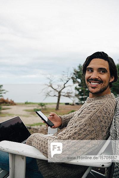 Lächelnder Mann mit Laptop und Mobiltelefon schaut weg  während er auf einem Stuhl gegen den Himmel sitzt