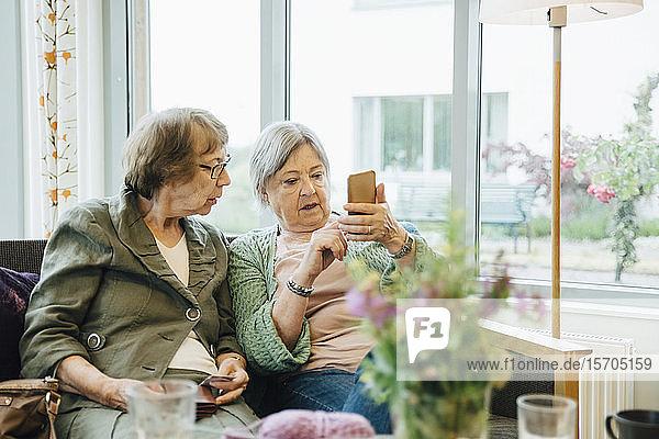 Ältere Frau benutzt Mobiltelefon  während sie mit einer Freundin auf dem Sofa vor dem Fenster des Altersheims sitzt