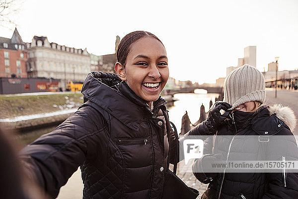 Porträt einer glücklichen Teenagerin  die mit einem Freund in der Stadt Unfug treibt