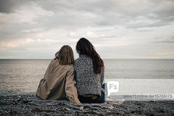 Rückansicht von Freundinnen  die ihre Freizeit am Strand verbringen  bei bewölktem Himmel