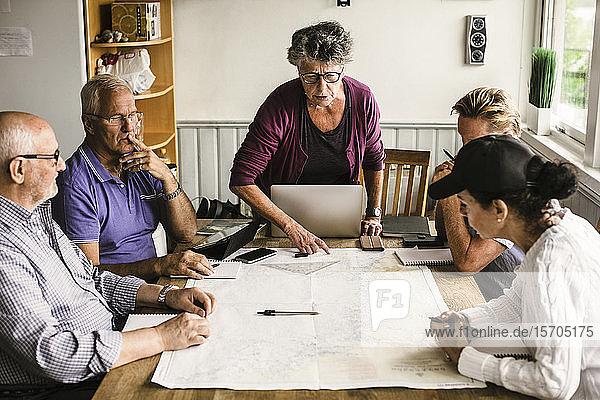 Weibliche Ausbilderin erklärt älteren Männern und Frauen während des Navigationskurses über Karte am Tisch