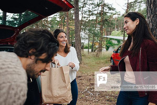 Lächelnde Freunde entladen Gepäck aus dem Auto  während sie sich im Hinterhof unterhalten