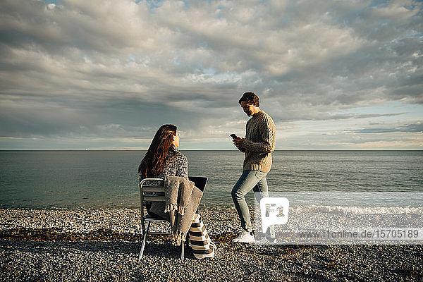 Mann benutzt Mobiltelefon  während Frau mit Laptop auf einem Stuhl am Strand gegen den Himmel sitzt