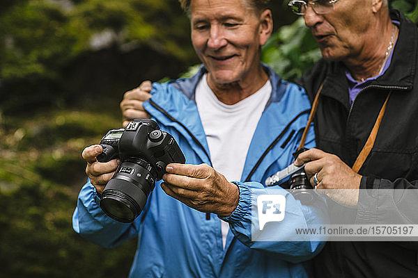 Älterer Mann zeigt einem männlichen Freund während eines Fotokurses Kamera